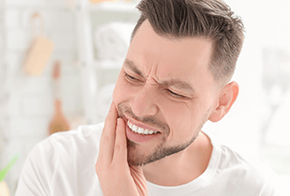 man with tooth pain needs an emergency dentist now
