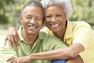 older couple smiling because they have healthy teeth with dental implants