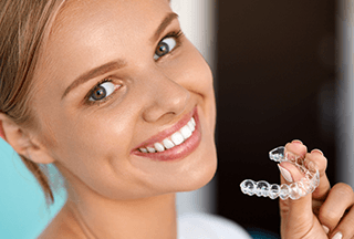 Lady smiling and holding an Invisalign clear aligner